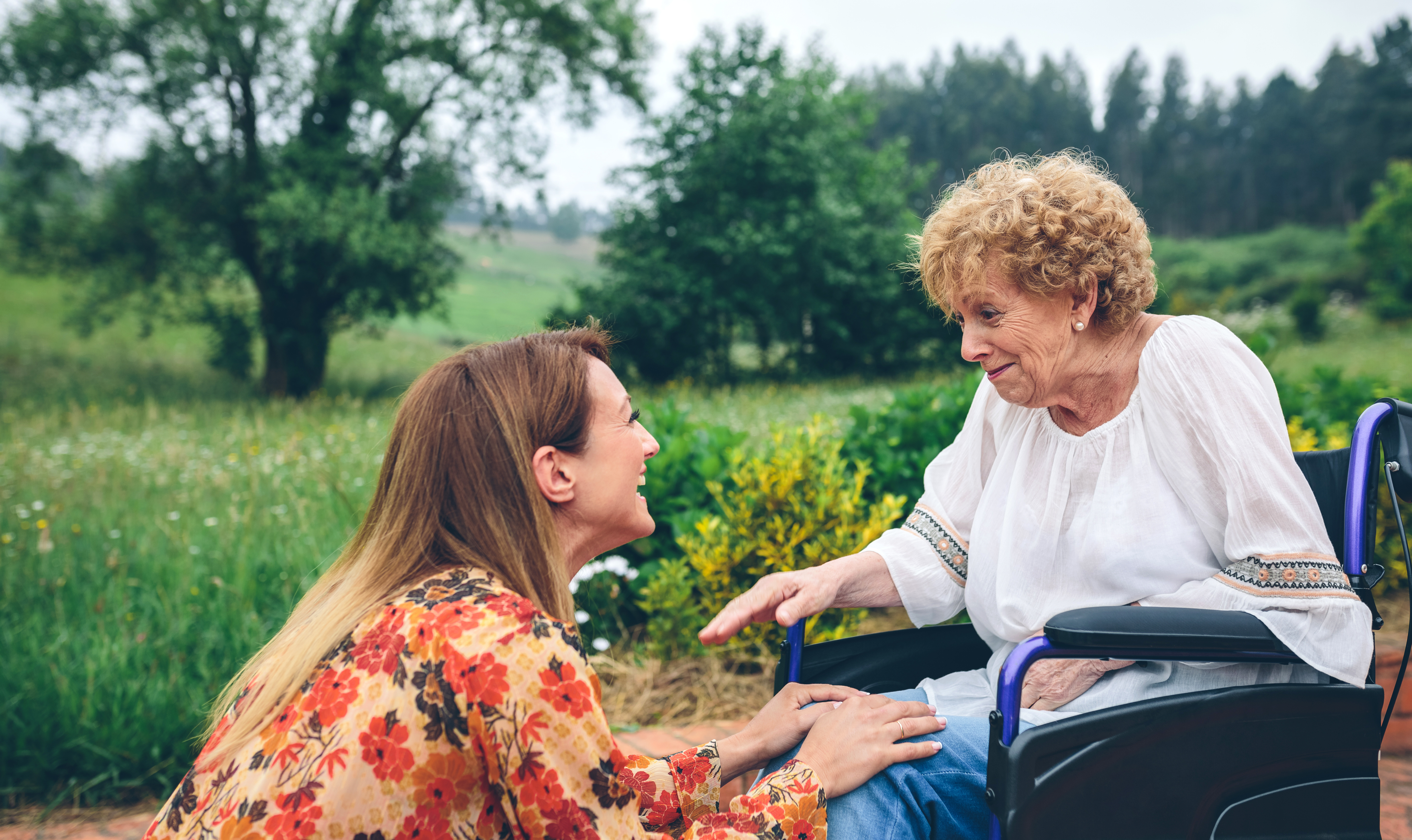 Affectionate young woman talking to elderly woman in a wheelchair in the garden