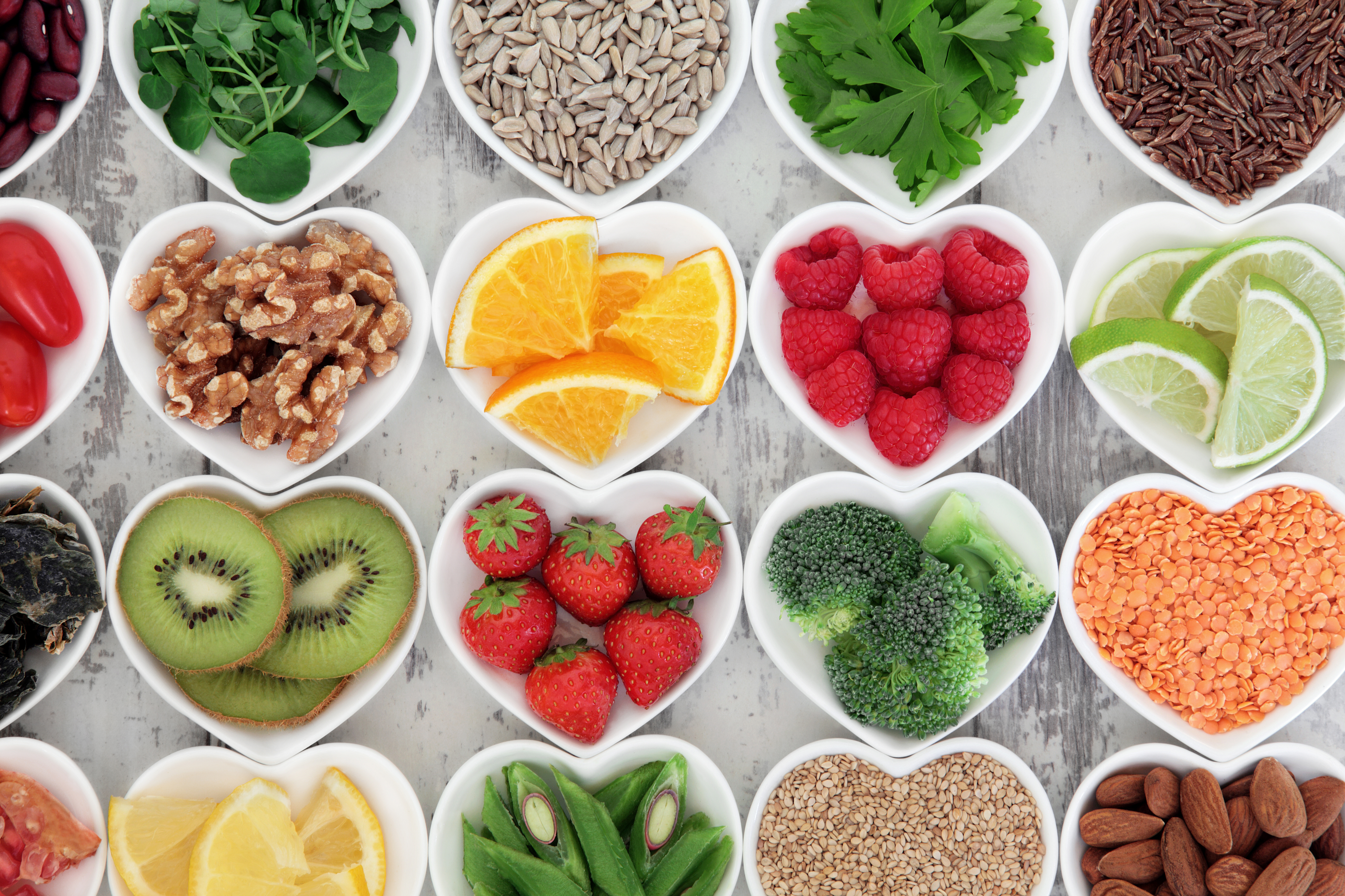 Super food selection for health diet in porcelain bowls over distressed wooden background.