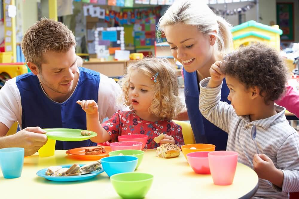 Childcare workers playing with children at a table
