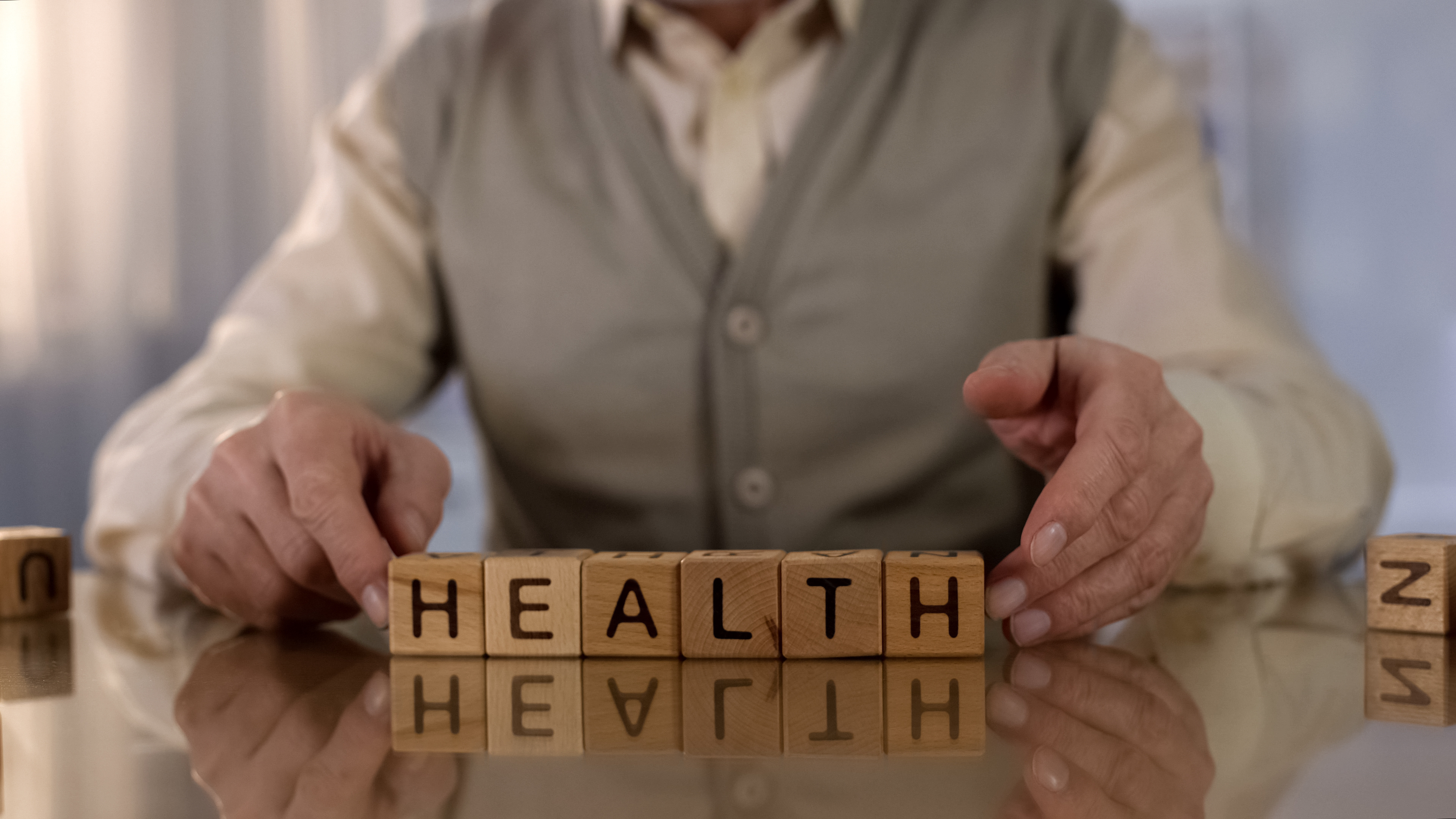 Grandfather making word health of wooden cubes on table, elder care, medicine